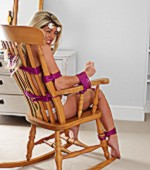 Cute blonde with supple boobs and hot booty tied to rocking chair with pink cords