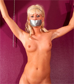 Beautiful enticing chick in restraints with hands, mouth and legs bound with rope