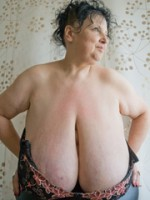 Curly brunette mature demonstrates her enormous boobs