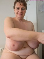 Big-titted milf putting on black stockings to look seductive