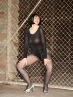 Brunette with red lips in sheer leotard and tights wearing open-toed shoes poses by a fence.