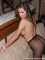 Athina is laying on the bed in pantyhose and blindfold waiting for her master