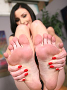 Gorgeous brunette milf in a black top enjoys inspecting her sexy feet with a nice pedicure