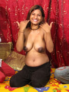 Long haired young indian babe in red lingerie stripteasing and flashing her huge juggs.