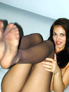 Perfect brunette beauty in tight nylons taking high heeled shoes out of her feet.