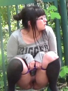Prankish girl pees onto a bench at a camping site