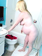 Ponytailed brunette preggo taking bath