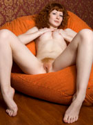 Fresh after shower naked redhead beauty moisturizing her perfect body with oil.