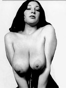Playful busty vintage beauty smoking and seductively posing.